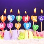 bolo de aniversário com velas em fundo violeta — Fotografia Stock  #46439831