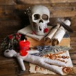 Conceptual photo of love magic. Composition with skull, voodoo doll, dried herbs and candle on dark wooden background — Stock Photo #46444869
