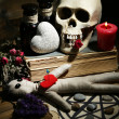 Conceptual photo of love magic. Composition with skull, voodoo doll, dried herbs and candle on  dark wooden background — Stock Photo #46444903