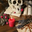 Conceptual photo of love magic. Composition with skull, voodoo doll, dried herbs and candle on dark wooden background — Stock Photo #46444929