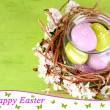 Composition with Easter eggs and blooming branches in glass jar and decorative nest, on color wooden background — Stock Photo