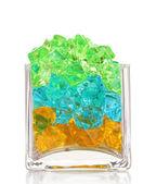 Een glas met kleurrijke decoratieve stenen geïsoleerd op wit — Stockfoto