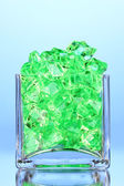 A glass with green decorative stones on blue background close-up — Foto Stock