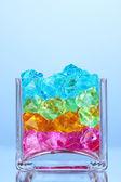 Um copo com pedras decorativas coloridas no grande plano de fundo azul — Foto Stock