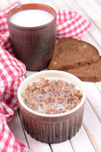 Boiled buckwheat with milk in bowl on table close-up — Stock fotografie