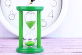 Hourglass and big clock on light background — Zdjęcie stockowe