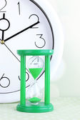 Hourglass and big clock on light background — Stock Photo