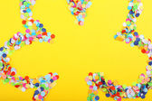 Confetti in shape of flower on yellow background — Stock Photo