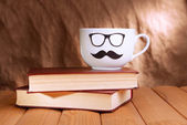 Cup with mustache on table on brown background — Stock fotografie