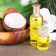 Coconuts and coconut oil on wooden table, on nature background — Stock Photo #46453877