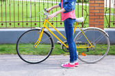 Young woman with bicycle outdoors — Stock Photo