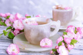 Beautiful fruit blossom with cup of tea on table on grey background — Stock Photo