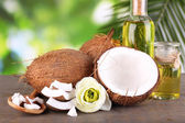 Coconuts and coconut oil on wooden table, on nature background — Stock fotografie