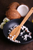 Coconuts on pan on wooden table — Stock Photo