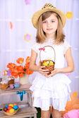 Krásná malá dívka drží košík s barevné vejce na dekorativní pozadí — Stock fotografie