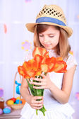 Beautiful small girl holding flowers on decorative background — Foto de Stock