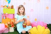 Belle petite fille tenant panier avec coloré des œufs sur fond décoratif — Photo