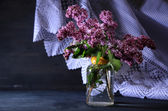 Beautiful lilac flowers in vase, on color wooden background — Foto Stock