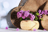 カラー木製テーブル、明るい背景上で籐製の花瓶に美しいライラック色の花 — ストック写真