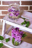 Beautiful lilac flowers in vases, on wooden ladder, on color wall background — Foto Stock