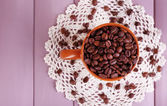 Cup full of coffee beans on color wooden background — Stock fotografie