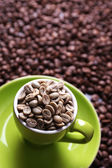 Cup full of green coffee beans on brown coffee beans background — Stock Photo
