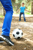 Happy dad and son playing football in the park — Стоковое фото