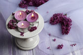 Beautiful candles and lilac flowers on wooden table — Stock Photo