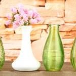 Different decorative vases on shelf on brick wall background — Stock Photo
