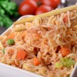 Tasty instant noodles with vegetables in bowl on table close-up — Stock Photo #46493621