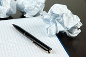 Crumpled paper balls with notebook and pen on wooden background — Stock Photo