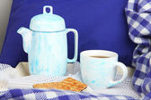 Cup and teapot with cookies on bed close up — Stock Photo