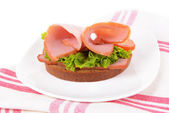 Delicious sandwiches with lettuce and ham on plate close-up — Stockfoto