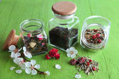 Assortment of herbs and tea in glass jars on wooden background  — Stok fotoğraf