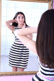 Beautiful girl trying dress near mirror in room — Stock Photo