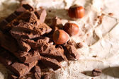 Chopped bar of chocolate on light background — Stockfoto