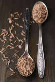 Spice cumin in spoons on wooden background — Stock Photo