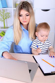 Pretty woman with baby working at home — Stock Photo
