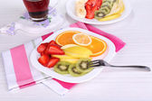 Various sliced fruits on plates on table close-up — Stockfoto