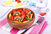 Various sliced fruits in bowl on table close-up — Stockfoto
