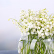 Постер, плакат: Beautiful lilies of the valley in glass vase on light background