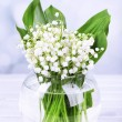 Постер, плакат: Beautiful lilies of the valley in glass vase on wooden table