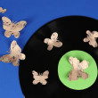 Old vinyl record with paper butterflies, on blue background — Stock Photo #46539315