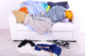 Messy colorful male clothing on  sofa on light background — Stock Photo