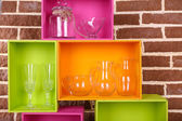 Beautiful colorful shelves with tableware  on  brown  wall background — Stock Photo