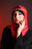 Beautiful muslim arabic woman on dark color background — Stock Photo