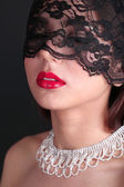 Girl with red lips and openwork black eye shades on dark background — Stock Photo
