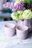 Composition with tea mugs and beautiful spring flowers in vase, on wooden table, on bright background — Foto de Stock