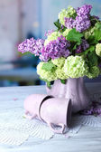 Composition with tea mugs and beautiful spring flowers in vase, on wooden table, on bright background — ストック写真