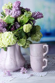 Composition with tea mugs and beautiful spring flowers in vase, on wooden table, on bright background — Stok fotoğraf